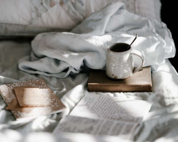 book and coffee on bed