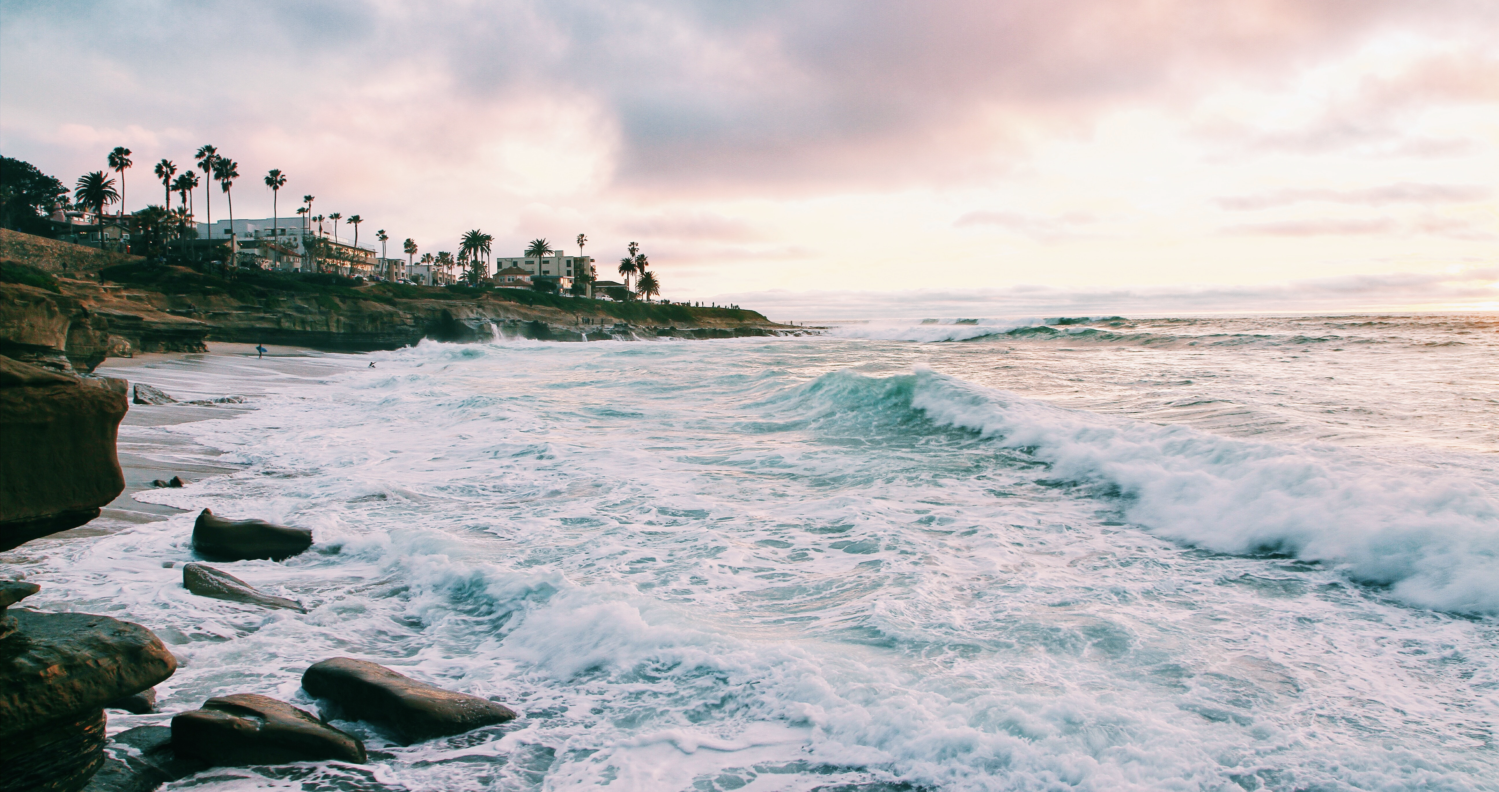sea waves crashing on san diego shore during golden hour